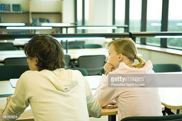 'Two college students sitting at table in library, rear view'