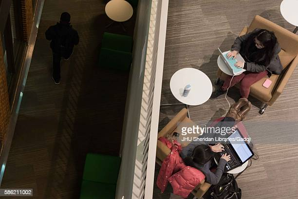 Two college students study on their laptops in the Brody Learning Commons, a collaborative/interactive study space and library on the Homewood campus...