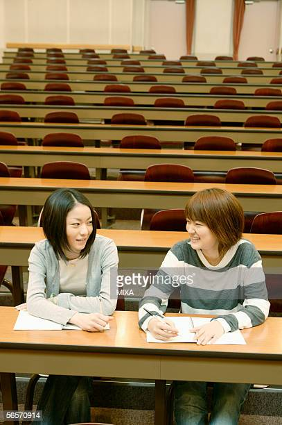 Two college students studying and talking in lecture hall