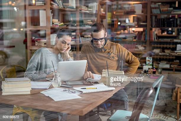 Two college students studying for the exams in library.