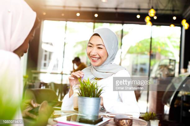 Two college students with hijab talking and smiling in a cafe