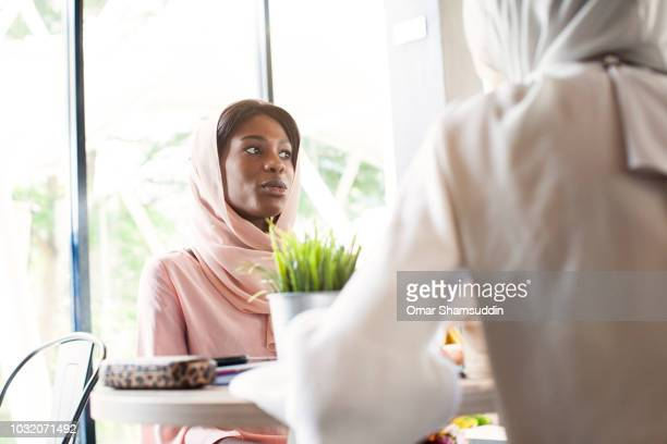 Two college students with hijab talking in a cafe