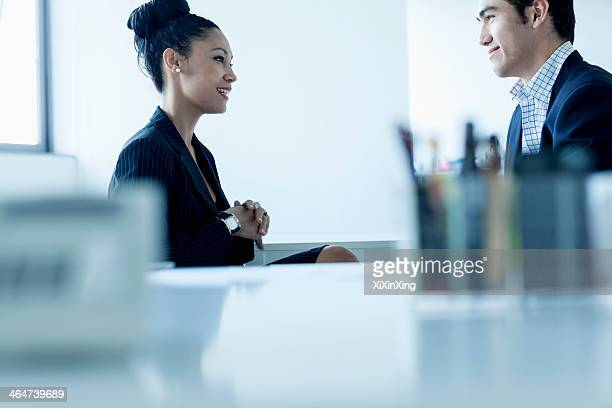 Two colleges smiling and talking by the desk in the office