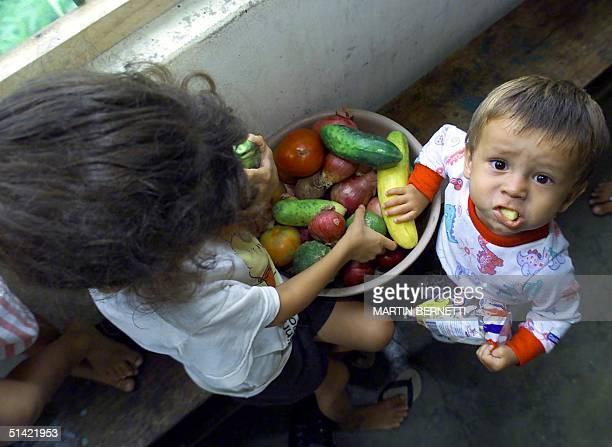 Two Colombian refugee children hold vegetables in the kitchen 08 December 2000 in Lago Agrio Ecuador Dos ninos colombianos toman frutas en la cocina...