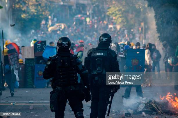 Two Colombia's riot police officers stand as demonstrators clash as demonstrations ended in late-night clashes between riot police and Demonstrators...