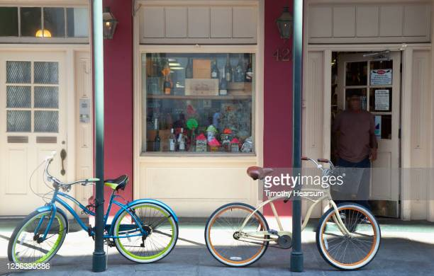 two colorful bicycles locked to street sign posts in front of a shop - timothy hearsum stock pictures, royalty-free photos & images