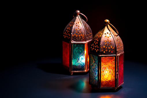 Two colorful oriental Lamp lanterns burn with candles with color reflection on dark black background for Ramadan and other islamic muslim holidays 930726334