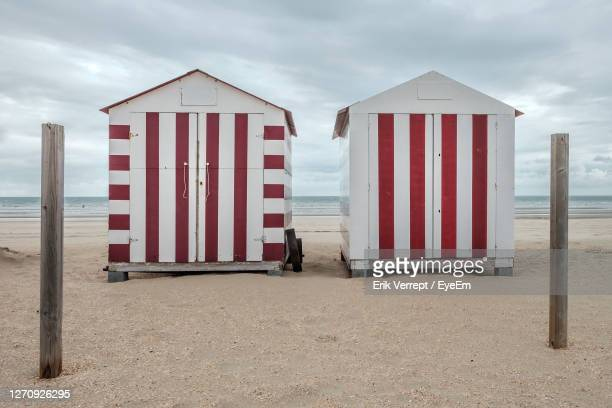 two colourful beach huts on a deserted beach against cloudy sky - belgische cultuur stockfoto's en -beelden