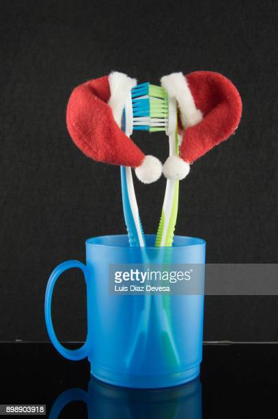 two colourful soft toothbrushes in blue cup