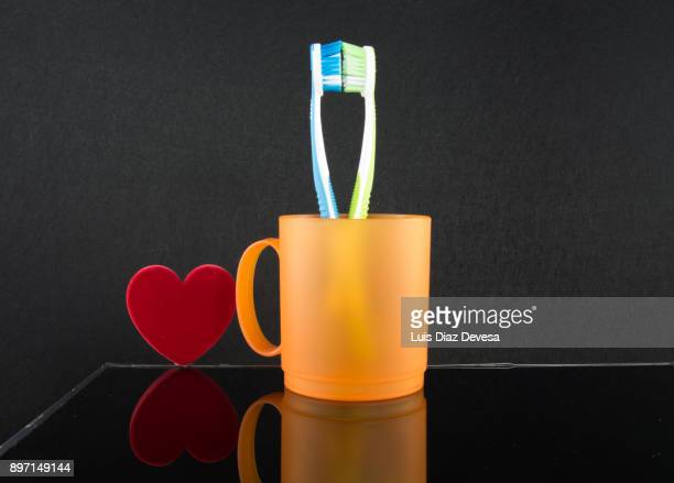 two colourful soft toothbrushes in orange cup