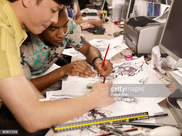 two comic book artists working on their artwork