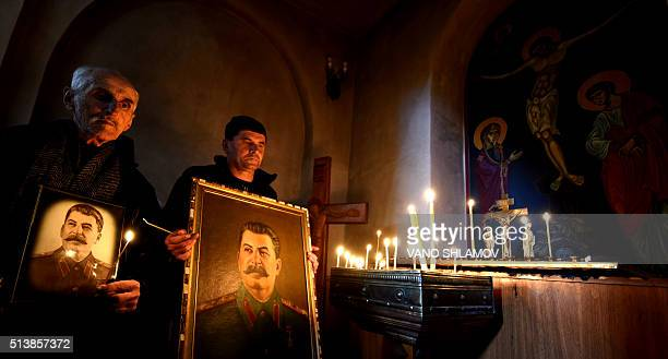 Two communist party supporters hold candles and portraits of late Soviet dictator Joseph Stalin at a church in Stalin's native town of Gori some 80...