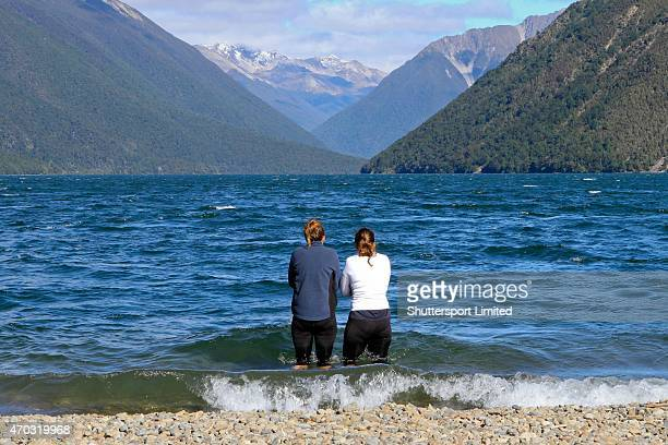 Two competitors cool off in the shallows of Lake Rotoiti following the 2015 Alpine Lodge Loop The Lake trail run at Lake Rotoiti on April 18 2015 in...
