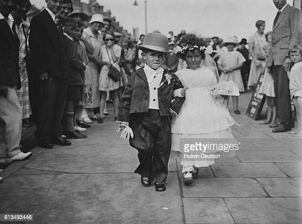 Two competitors for the children's fancy dress competition stroll arminarm past a crowd of onlookers at Sandown fete