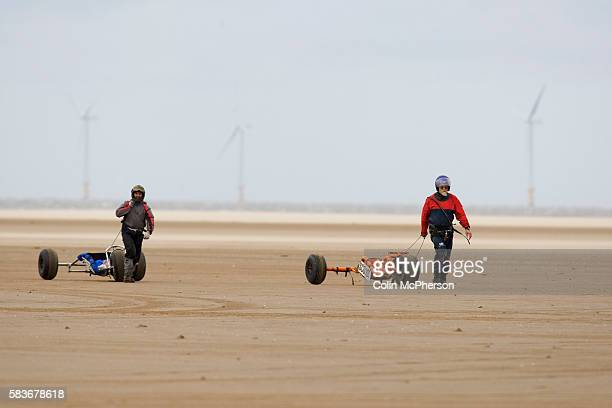 Two competitors pulling their buggies across the course after taking part in one of the races at the European Kite Buggy Championships at Hoylake...