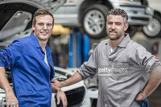 Two confident car mechanics in repair garage