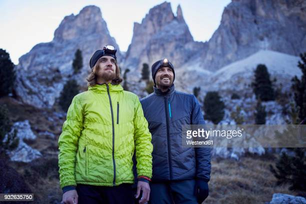 Two confident men wearing headlamps in the mountains