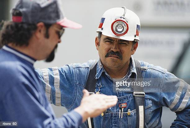 two construction or mining workers discuss their job