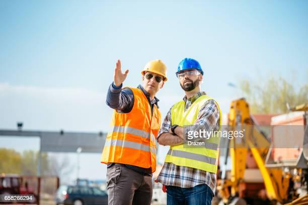 Zwei Bauarbeiter - Ingenieure auf der Baustelle, die nächste Bauphase vereinbaren