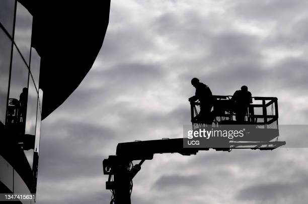 Two construction workers in silhouette against grey sky on a hydraulic lifting ramp.