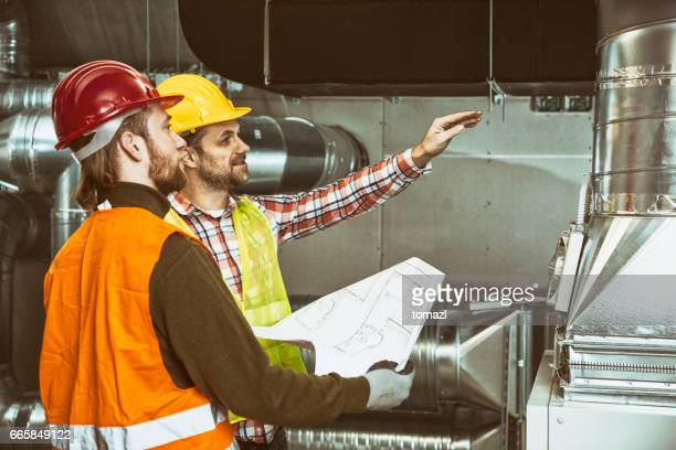 Two construction workers looking at plan and discussing the HVAC