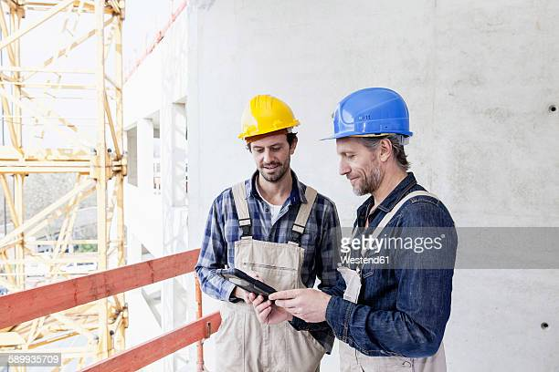 Two construction workers on construction site looking at digital tablet
