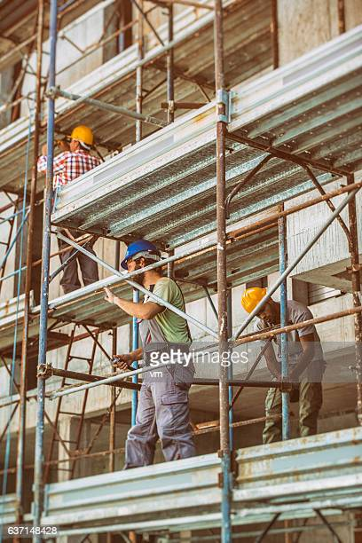 Two construction workers on scaffolding