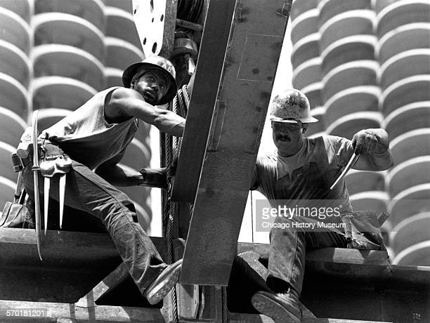 Two construction workers placing a beam at 35 West Wacker Chicago Illinois 1987 Marina City towers visible in the background