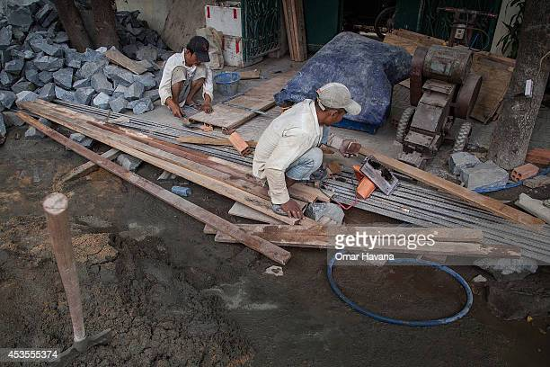 Two construction workers prepare wood planks in the street to be used for a new building on August 13 2014 in Phnom Penh Cambodia After months of...