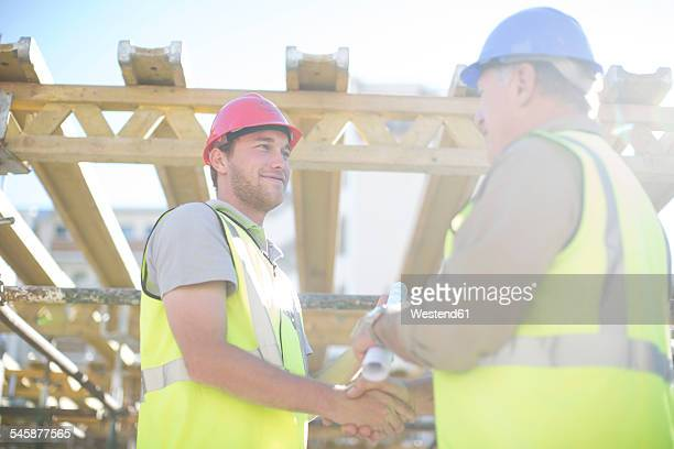 Two construction workers shaking hands in construction site