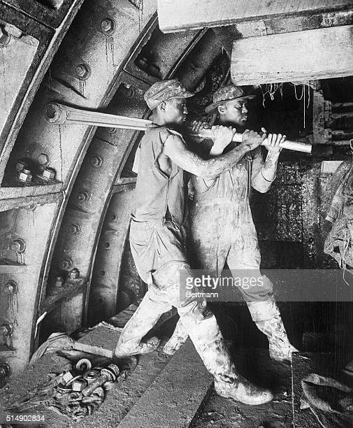 Two construction workers tighten a rivet during construction of the Holland Tunnel