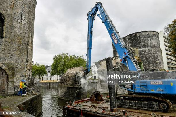 "Two construction workers watch as the ""Pont des Trous"" medieval bridge is being demolished by a crane in Tournai, where the Scheldt river will be..."