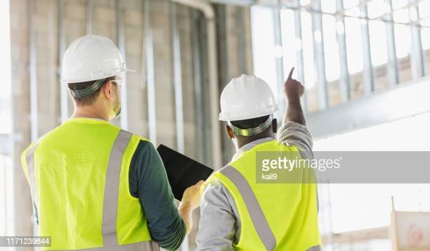 two construction workers with digital tablet - reflective clothing stock pictures, royalty-free photos & images