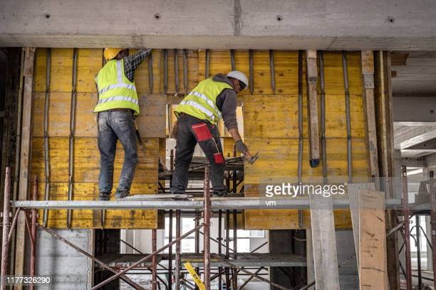 two construction workers working on a scaffolding platform - construction worker stock pictures, royalty-free photos & images