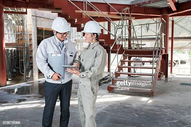 2 つの構造、同僚を見ているデジタルタブレット
