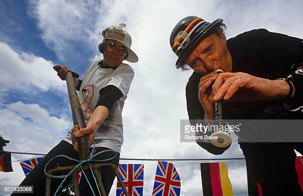 Two contestants of the world worm charming competition bend down to use a fork and a recorder to encourage invertebrates out of the ground in a field...