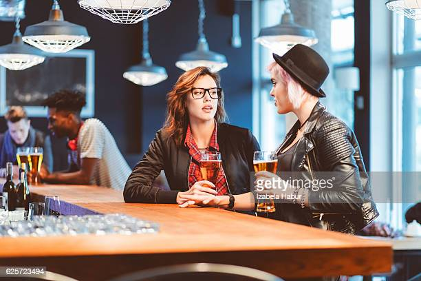 Two cool girls drinking beer in a pub