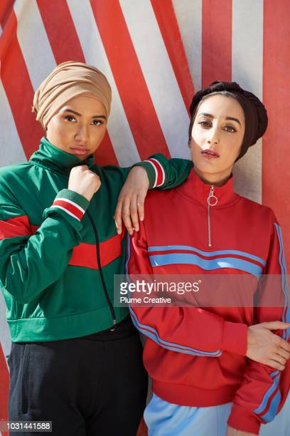 Two cool muslim women against striped background