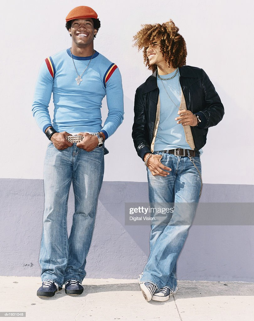 Two Cool Twentysomething Men Wearing Jeans Leaning on a Wall : Stock Photo