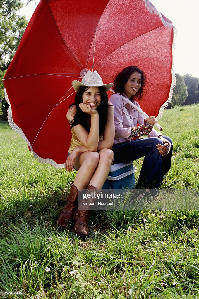 Two Cool Women Sitting Side by Side Underneath a Parasol : Stock Photo