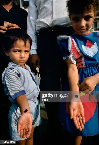 Two Coptic children show their tattoos which attest to their belonging to the Coptic community in Cairo