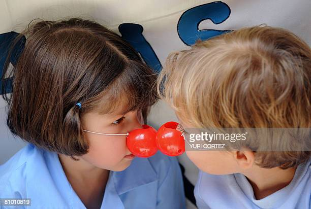 Two Costa Rican children touch with their red plastic noses as they wait for the arrival of US doctor Hunter Patch Adams at the Children Hospital in...