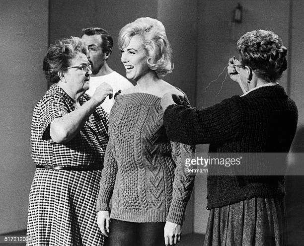 Two costumers attend to a laughing Marilyn Monroe as she prepares to rehearse a dance routine for the film Let's Make Love. Choreographer Jack Cole...