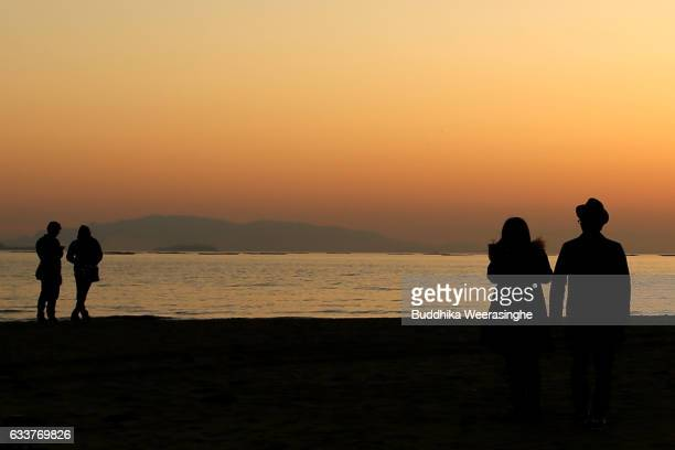 Two couple look sunset as they enjoy during the first day of spring at the Shinmaiko beach on February 4 2017 in Tatsuno Hyogo Prefecture Japan The...