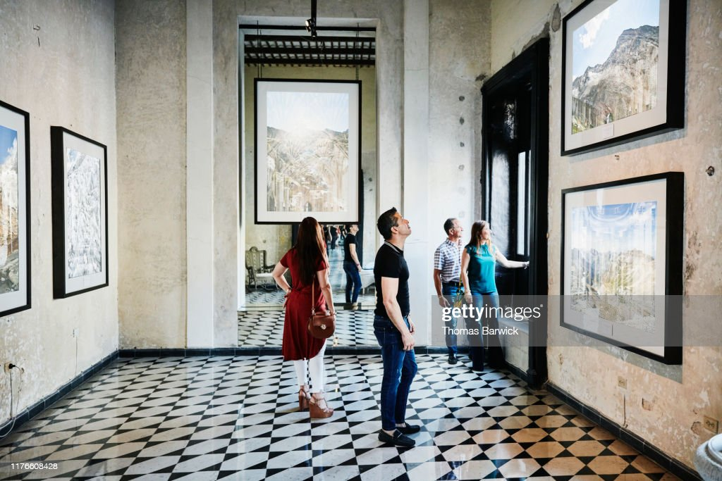 Two couples admiring artwork while touring museum during vacation : Stock Photo