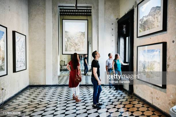 two couples admiring artwork while touring museum during vacation - konstmuseum bildbanksfoton och bilder