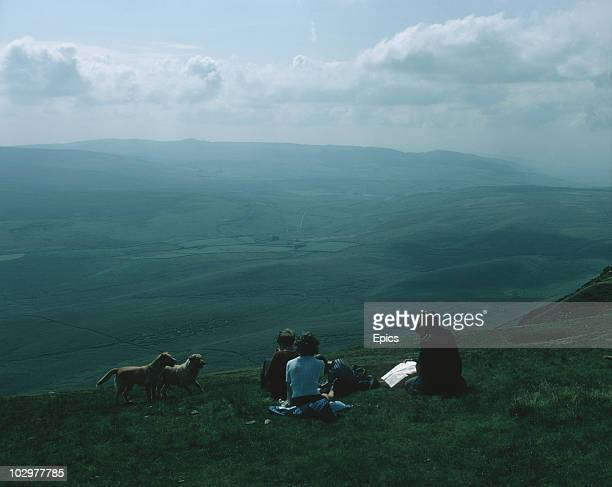 Two couples and their dogs take a rest to consult their maps and take in the view from Penyghent mountain in the Yorkshire Dales September 1970
