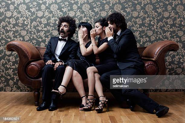 Two couples are sitting on sofa and whispering gossips