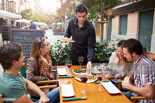 two couples at café. one couple looking at phone - klaus vedfelt mallorca stock pictures, royalty-free photos & images