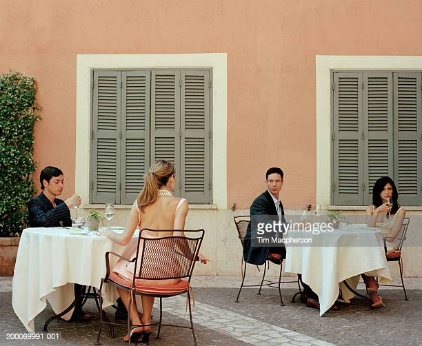 Two couples at cafe tables, woman looking at man at opposite table